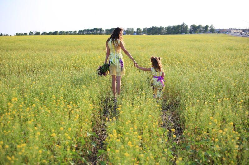 Молодая женщина с маленькой девочкой идут по зеленому полю