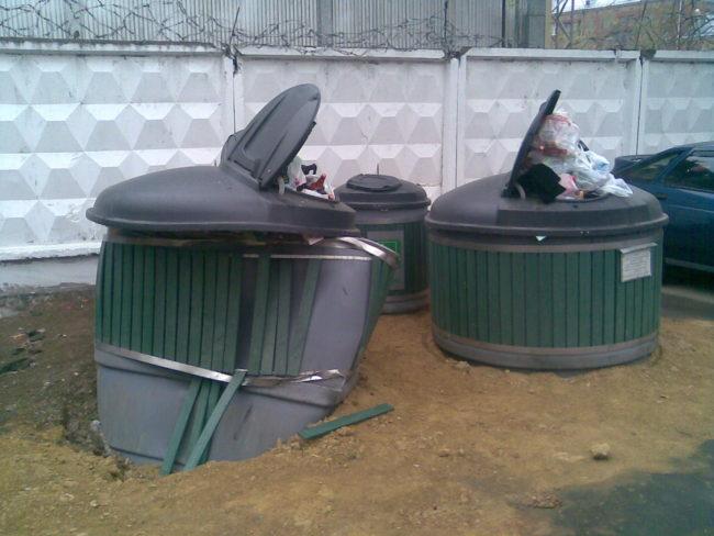 Сломанный и переполненный заглубленный контейнер для сбора мусора
